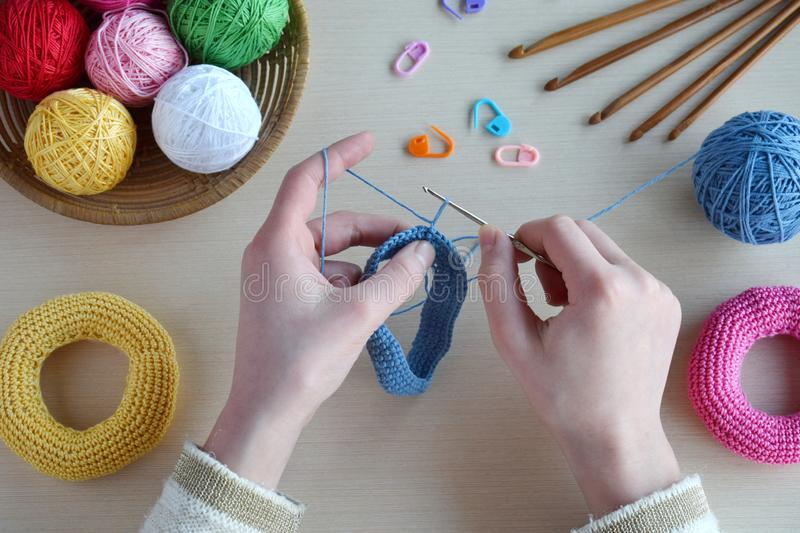 Making crochet pyramid from colored rings. Toy for babies and toddlers to learn mechanical skills and colors. On the table threads. Needles, hook, cotton yarn stock photo