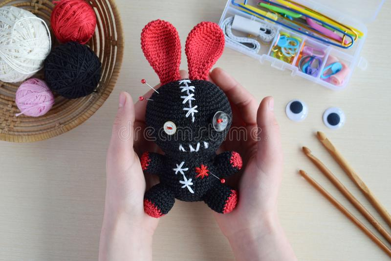 Making crochet voodoo rabbit. Toy for Halloween.  On the table threads, hook, cotton yarn. Handmade gift. Mystic, occult, horror. Making crochet voodoo rabbit royalty free stock photo