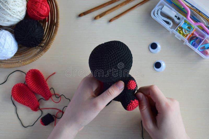 Making crochet voodoo rabbit. Toy for Halloween.  On the table threads, hook, cotton yarn. Handmade gift. Mystic, occult, horror. Making crochet voodoo rabbit stock photography
