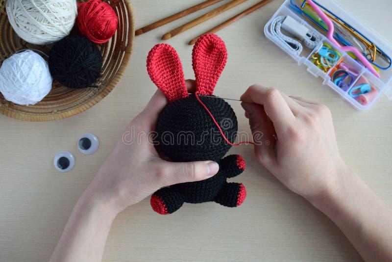 Making crochet voodoo rabbit. Toy for Halloween.  On the table threads, hook, cotton yarn. Handmade gift. Mystic, occult, horror. Making crochet voodoo rabbit stock image