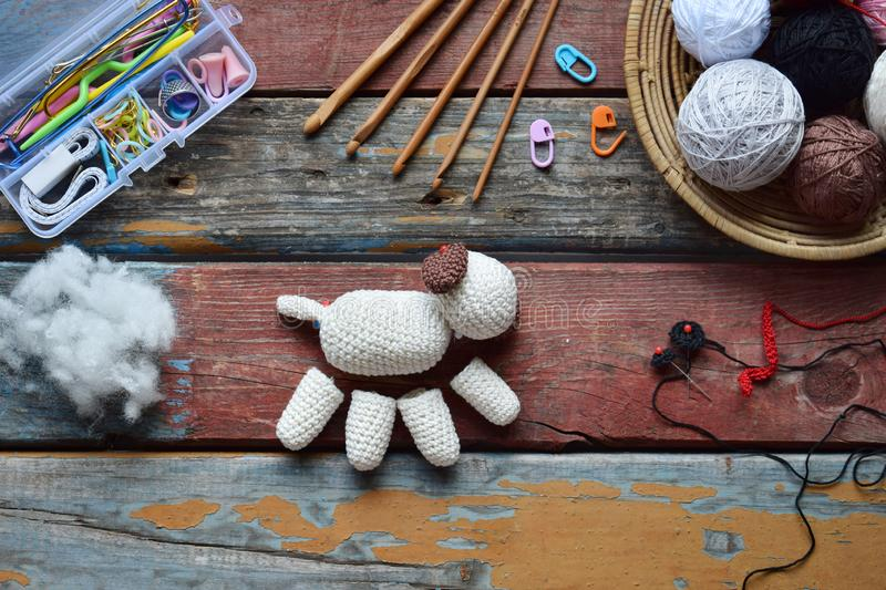 Making crochet white dog. Toy for babies or trinket.  On the table threads, needles, hook, cotton yarn. Handmade gift. Income from. Making crochet white dog. The royalty free stock photos