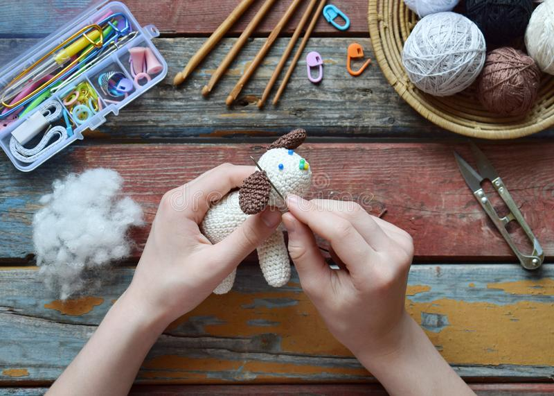 Making crochet white dog. Toy for babies or trinket.  On the table threads, needles, hook, cotton yarn. Handmade gift. Income from. Making crochet white dog. The royalty free stock photo