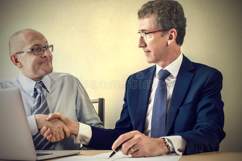 Making a deal. Two businessmen making a deal stock photos