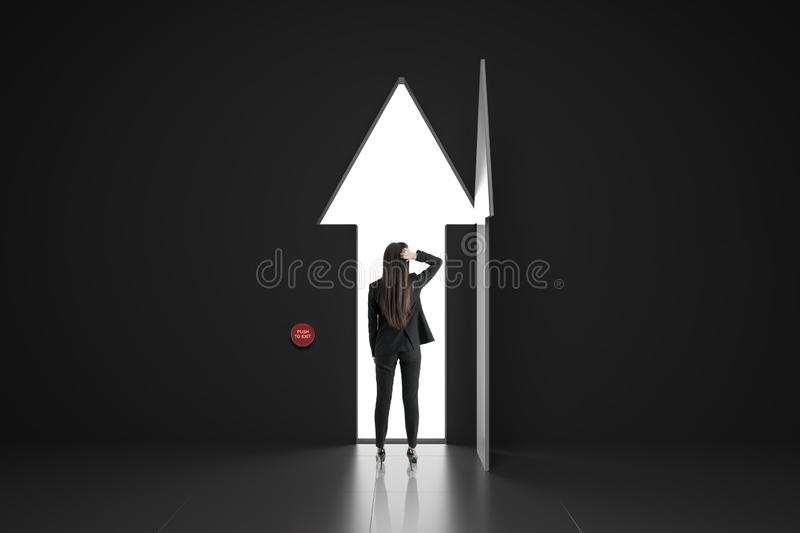 Making a decision concept with businesswoman. Walking through arrow door from dark room royalty free stock photo
