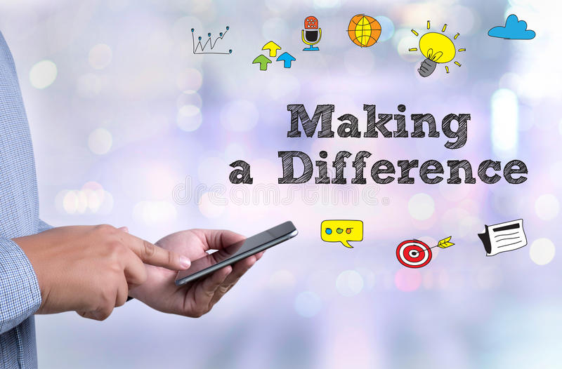 Making a Difference. Person holding a smartphone on blurred cityscape background royalty free stock images