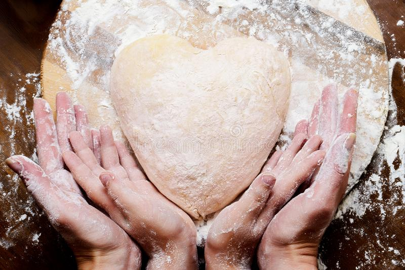 Making dough from eggs and milk. Heart shaped dough with female and child hands. Cooking and home concept.  royalty free stock photo