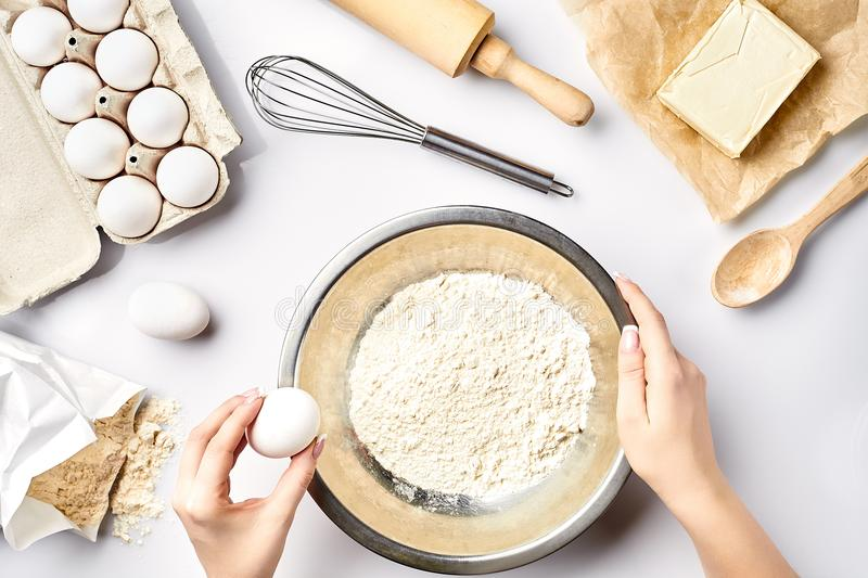 Making dough top view. Overhead of baker hands break egg on flour. Cooking ingredients for pastry on white table. royalty free stock image