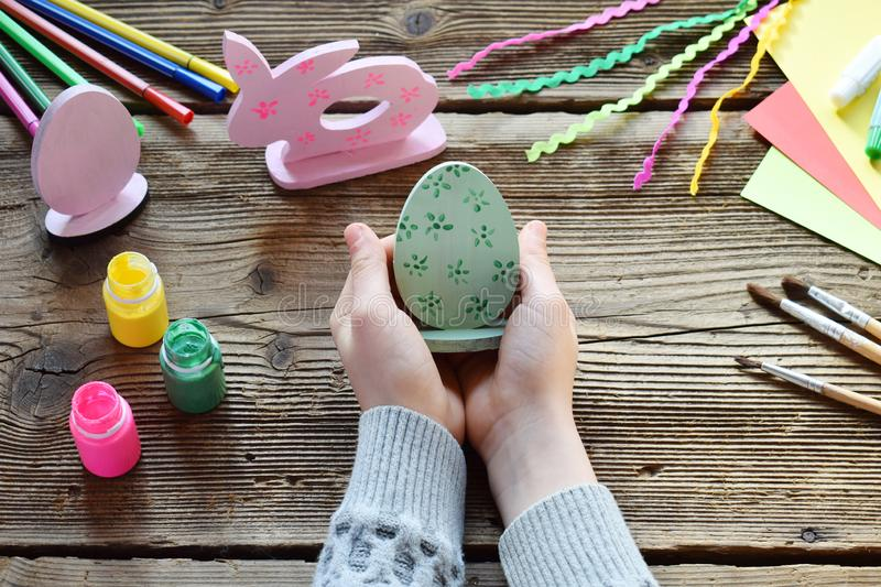 Making Easter decoration - easter eggs and bunny. Painting and coloring wooden toy of brushes and gouache. Creative process. royalty free stock photos