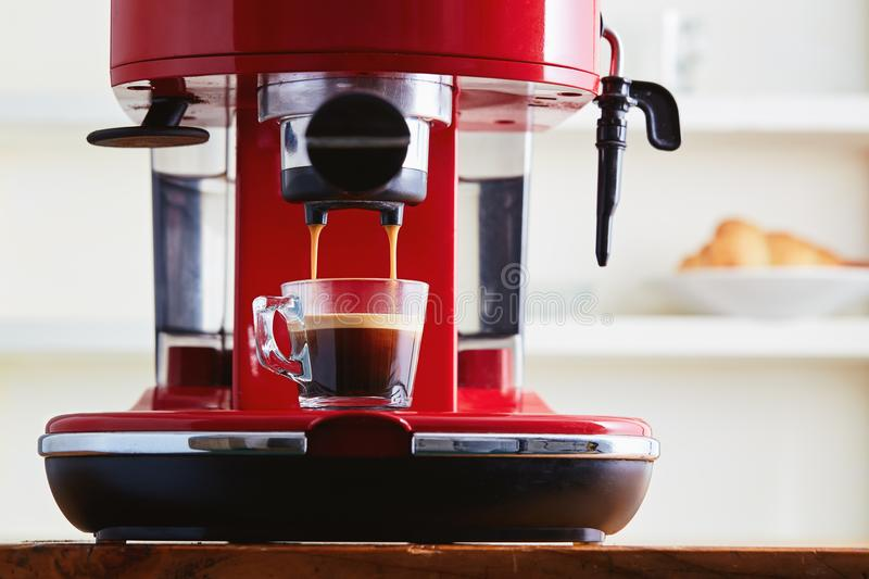 Making espresso in glass transparent coffee cup. royalty free stock photo
