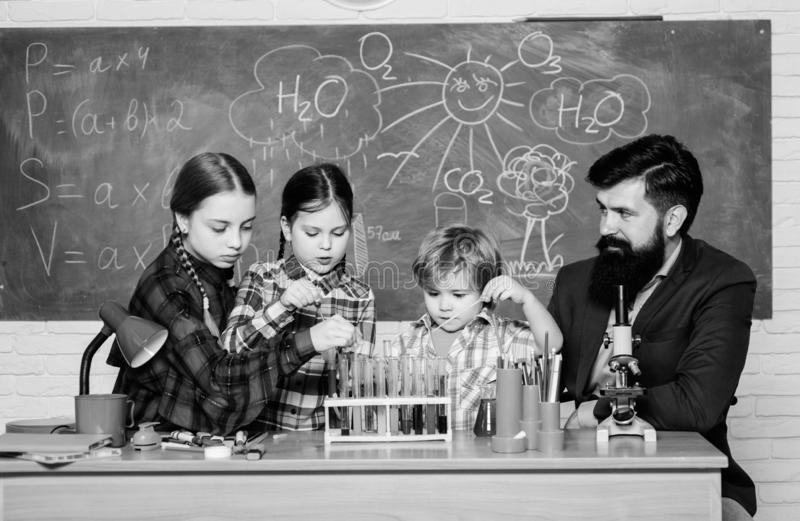 Making experiment in lab or chemical cabinet. back to school. chemistry lab. happy children teacher. kids in lab coat. Learning chemistry in school laboratory stock photography