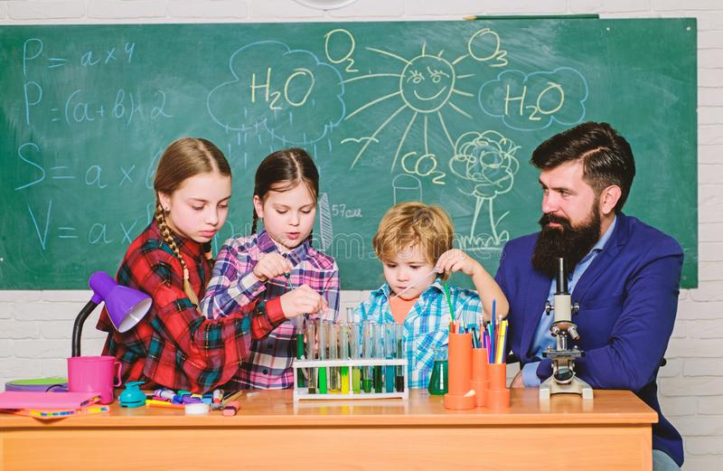 Making experiment in lab or chemical cabinet. back to school. chemistry lab. happy children teacher. kids in lab coat royalty free stock image