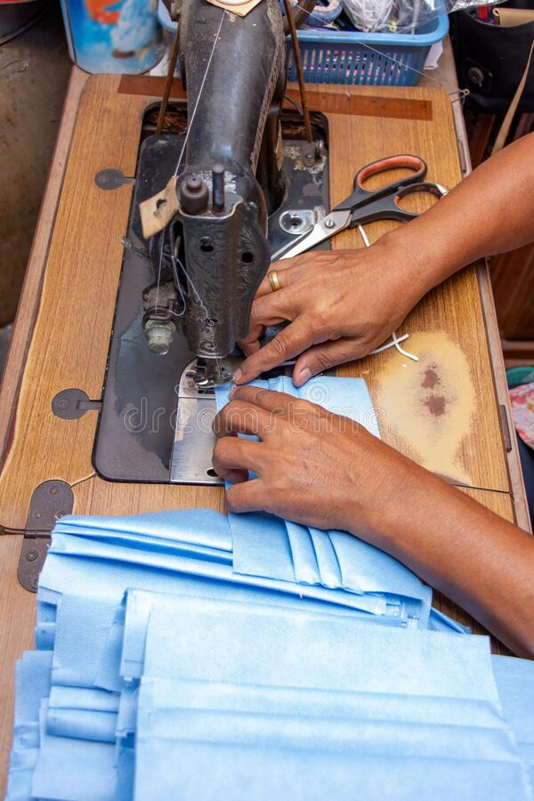 A making face masks from sterilization wrapping paper on a sewing machine. royalty free stock images