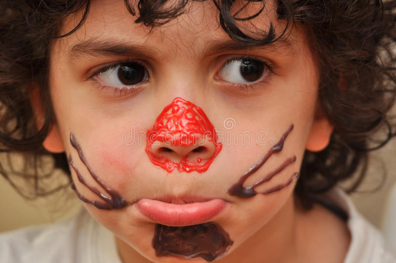 Hispanic Child Making Faces While Wearing a Syrup stock photo