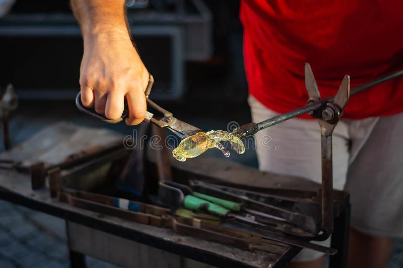 Making figurines from glass, just pulled out of the oven stock photos