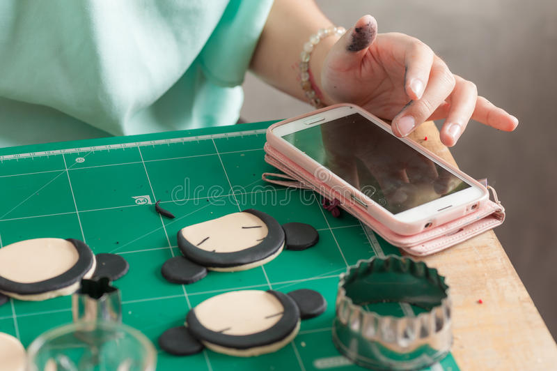 Making of fondant cake. Female hand touching smartphone while making fondant cake, fondant sugar mod action royalty free stock image