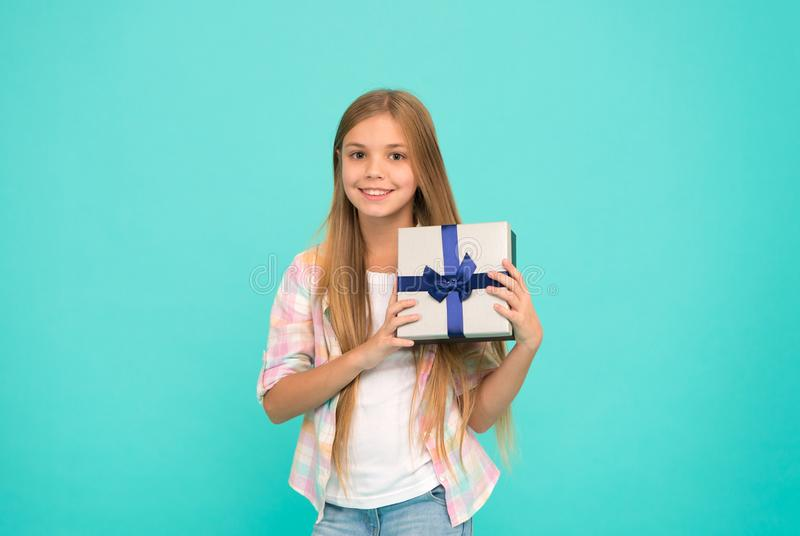 Making gift with soul. Little shopaholic with present wrapped in box. Small child holding gift box tied with ribbon bow. Small girl after shopping for gift stock photography