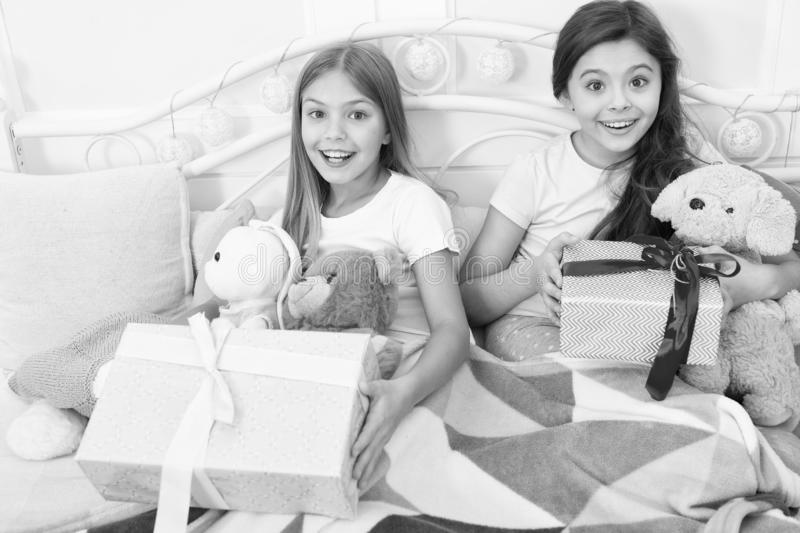 Making the gift time last longer. Happy small children hold gift boxes. New Year surprise. Cute small girls with stock images