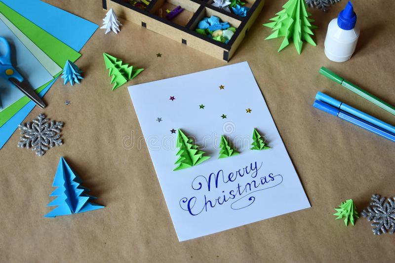 Making greeting card with origami 3D Xmas tree from paper. Merry Christmas and Happy New Year decoration. Children DIY concept. Handmade crafts on holiday with royalty free stock photography