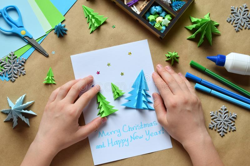 Making greeting card with origami 3D Xmas tree from paper. Merry Christmas and Happy New Year decoration. Childrens DIY concept. Making greeting card with royalty free stock photo