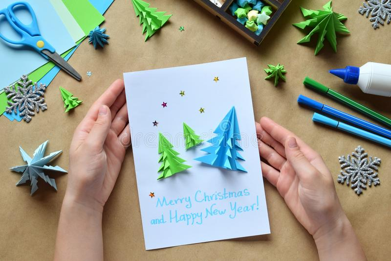 Making greeting card with origami 3D Xmas tree from paper. Merry Christmas and Happy New Year decoration. Childrens DIY concept. Making greeting card with royalty free stock photos