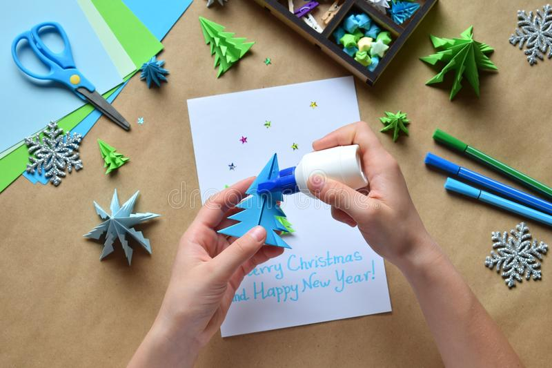 Making greeting card with origami 3D Xmas tree from paper. Merry Christmas and Happy New Year decoration. Childrens DIY concept. Handmade crafts on holiday stock image