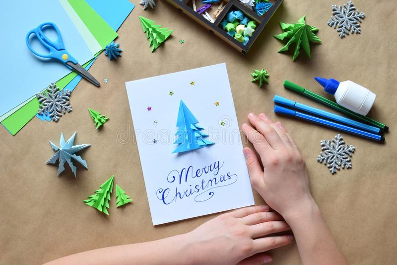 Making greeting card with origami 3D Xmas tree from paper. Merry Christmas and Happy New Year decoration. Childrens DIY concept. Handmade crafts on holiday stock photos