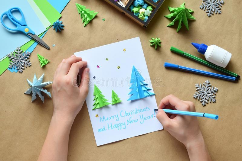Making greeting card with origami 3D Xmas tree from paper. Merry Christmas and Happy New Year decoration. Childrens DIY concept. Handmade crafts on holiday royalty free stock photos