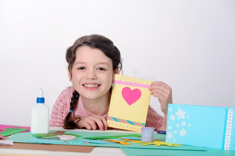 Making a greeting card. In school. Smiling little girl showing her work she did at art lesson. Valentine`s day craft royalty free stock image
