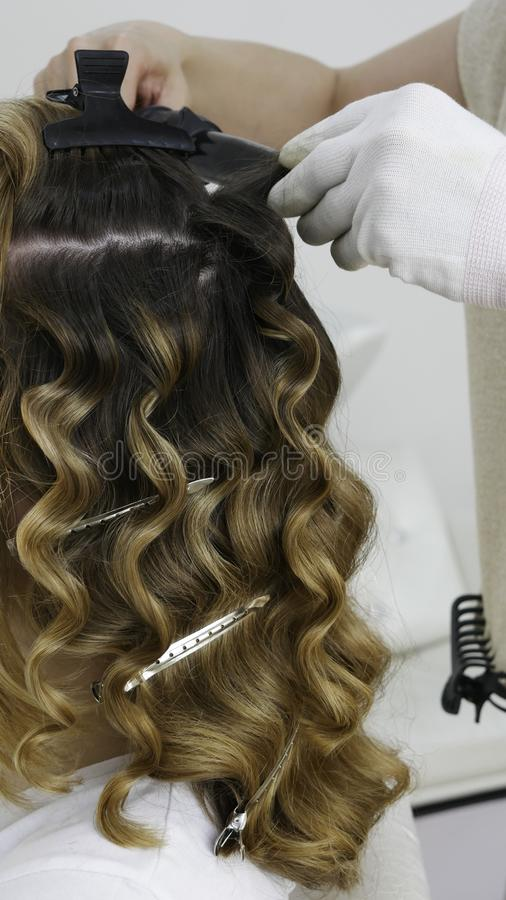 Making a hairstyle in the hair salon - close up royalty free stock image