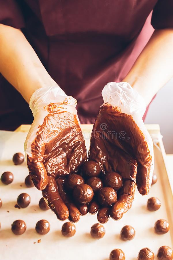Making handmade chocolates. Round chocolates doused with liquid chocolate in the hands of the confectioner chocolatier. Selective focus. Vertical frame royalty free stock photos