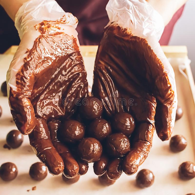Making handmade chocolates. Round chocolates doused with liquid chocolate in the hands of the confectioner chocolatier. Selective focus. Square frame Close-up stock image