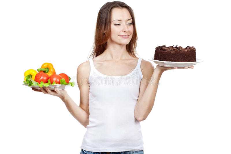 Making hard choice between vegetables and cake royalty free stock photo