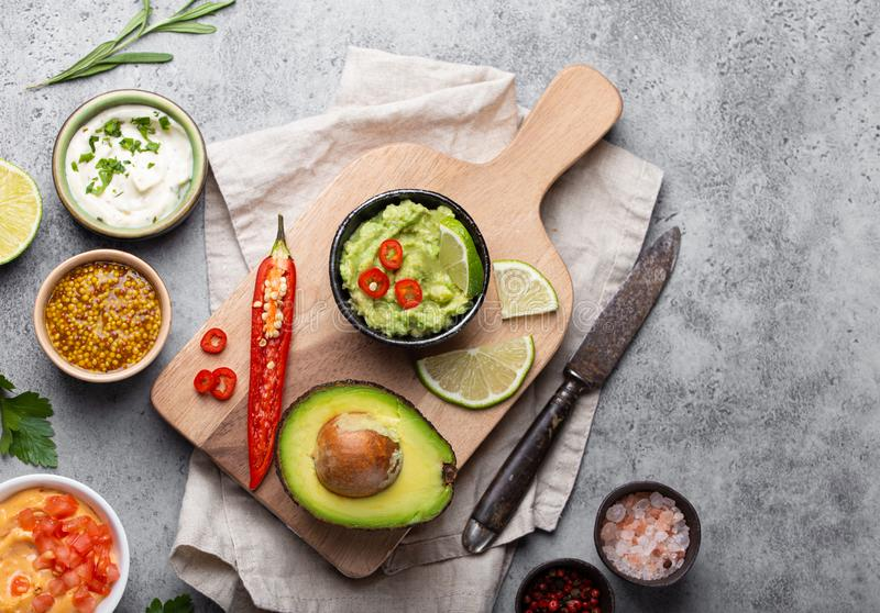 Fresh guacamole sauce. Making healthy green vegan guacamole sauce with fresh avocado, lime, chili pepper on wooden cutting board with old knife, stone rustic royalty free stock photography