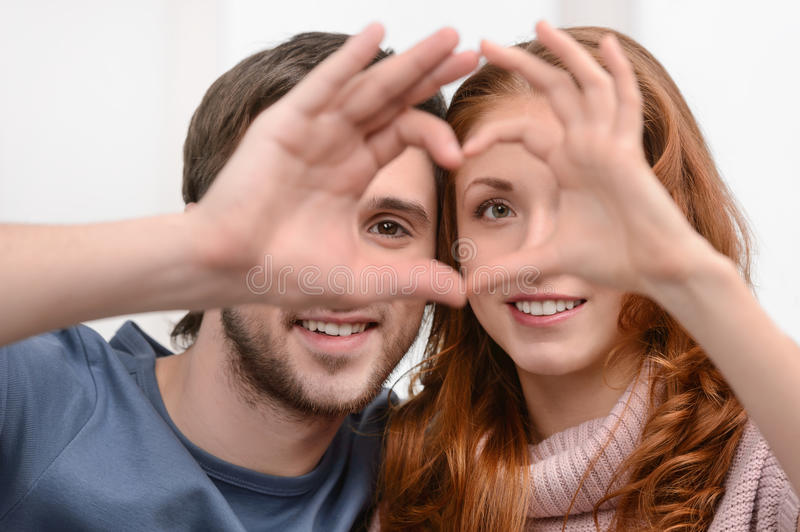 Making a heart. Attractive young couple making a heart with their hands royalty free stock photography