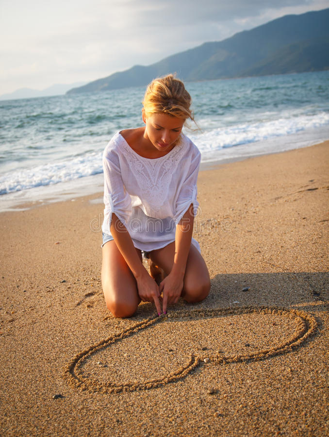 Making heart shape in sand stock photography