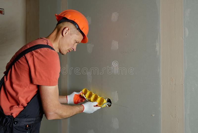 Making holes in the drywall royalty free stock image