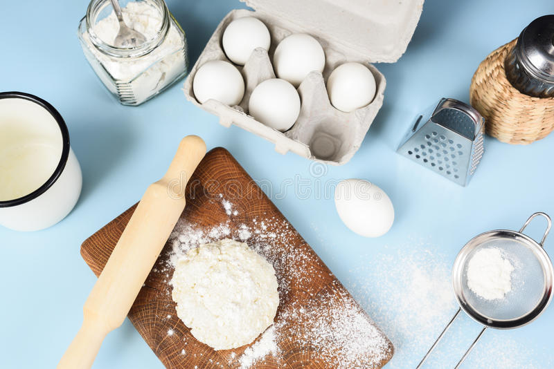 Making homemade cookies. Raw dough, rolling pin, sieve, eggs, fl. Our and icing sugar on blue table above view royalty free stock images
