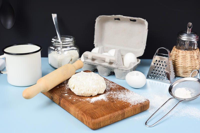 Making homemade cookies. Raw dough, rolling pin, sieve, eggs, fl. Our and icing sugar on blue table closeup royalty free stock photos