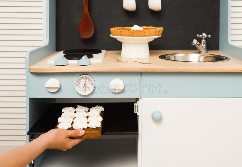 Making homemade desserts in toy kitchen. Meringues in stove and royalty free stock image