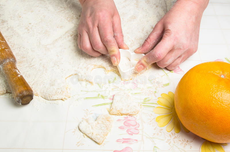 Making homemade sugar cookies. Woman's hands, form a dough and the flour on the table royalty free stock photos
