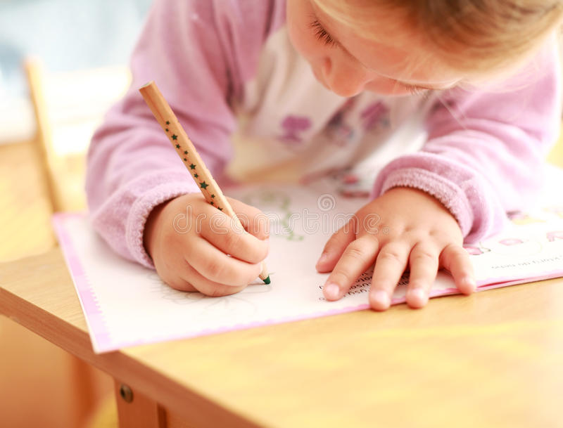 Making homework. Cute little girl painting at home royalty free stock images