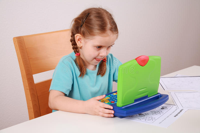Making homework. Cute little girl making homework with her computer royalty free stock image