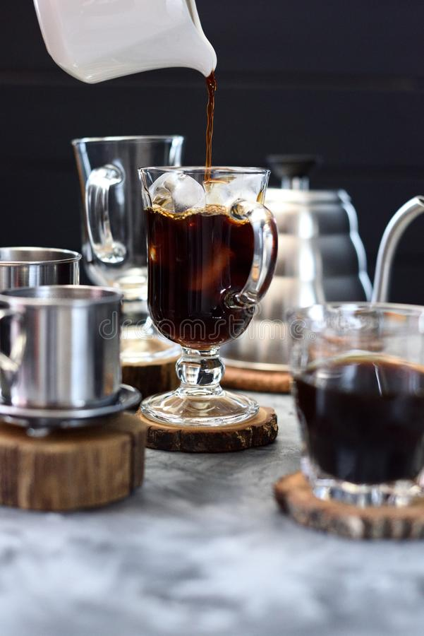 Making ice coffee. Pouring black coffee onto ice in tall glass on dark background. Copy space stock photos