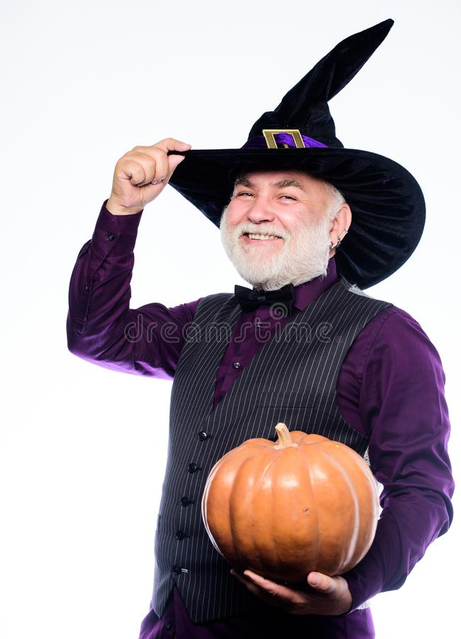 Making jack o lantern. mature man magician in witch hat. bearded man ready for halloween party. evil wizard hold orange stock photos