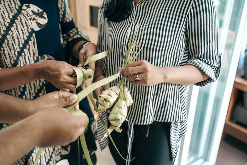 Making ketupat traditional indonesian food together. For eid mubarak celebration royalty free stock photos