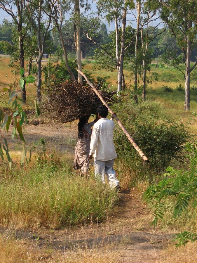 Making a living. A farmer and his wife walk miles with a load of burden with them to make small amount of money in India stock photography