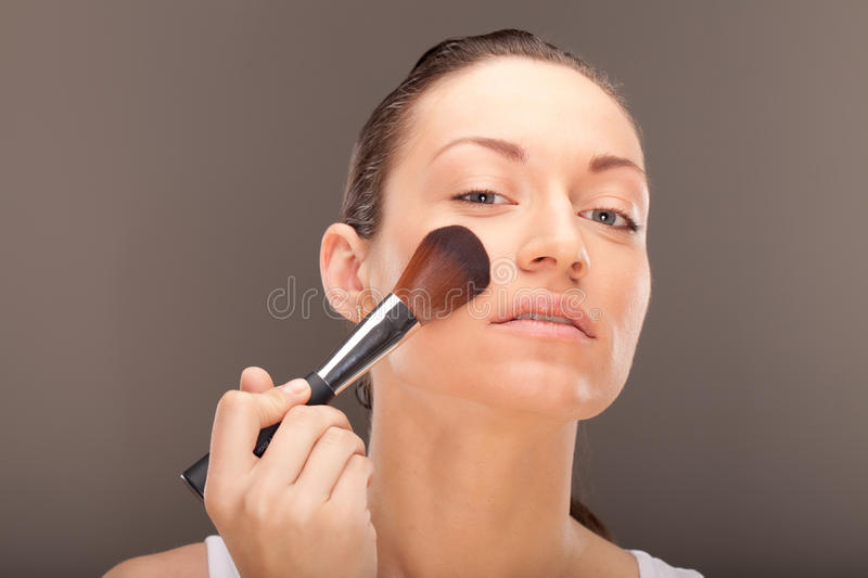 Making make-up. A young lady is preparing for an evening event stock image