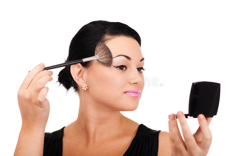Making make-up. A young lady is preparing for an evening event royalty free stock images