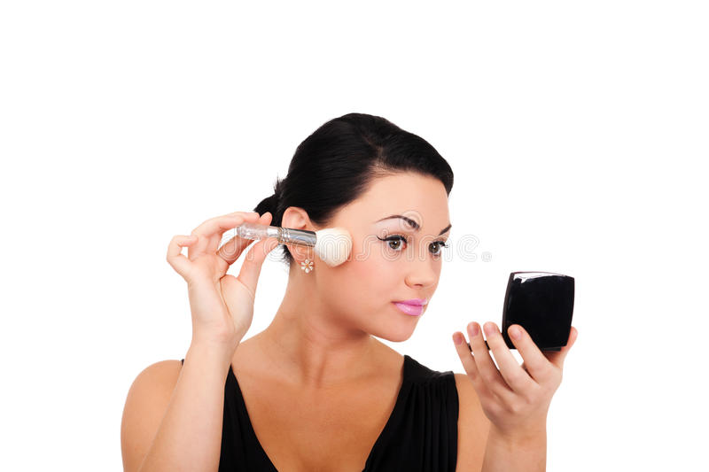 Making make-up. A young lady is preparing for an evening event royalty free stock photo