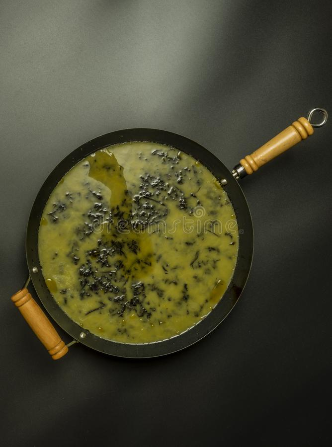 Making of marijuana butter with black background in wok. Making of marijuana green butter with black background in wok alternative buds cake cannabis cbd cookie royalty free stock photography